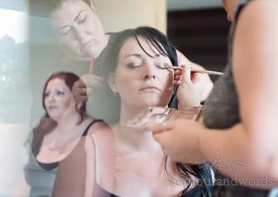 Bride has wedding make up and hair styled for Rock and roll wedding watched by bridesmaid