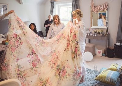 Bride holds floral wedding dress with bridesmaids before Lulworth castle wedding