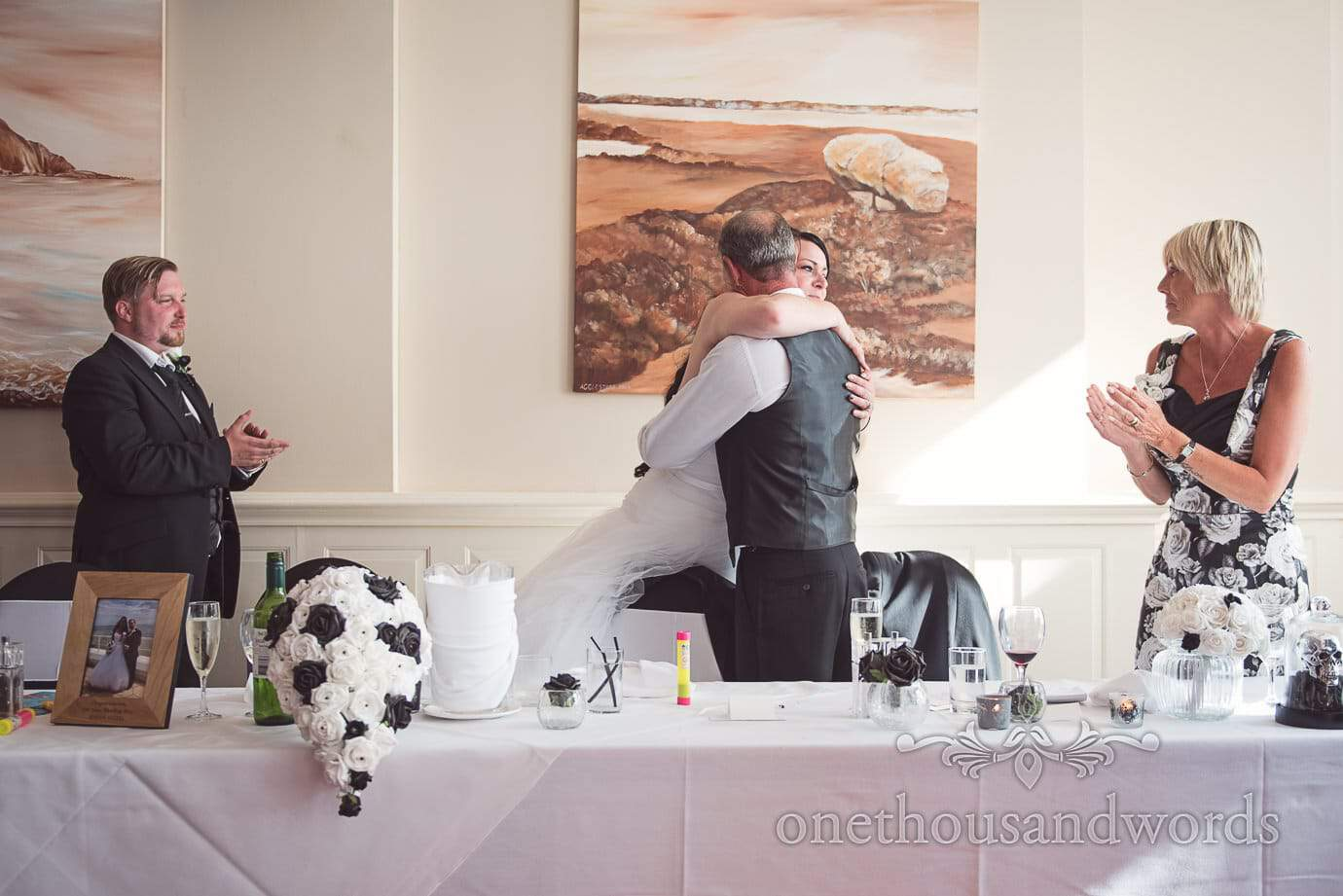 Bride hugs her father after his wedding speech at black and white themed wedding