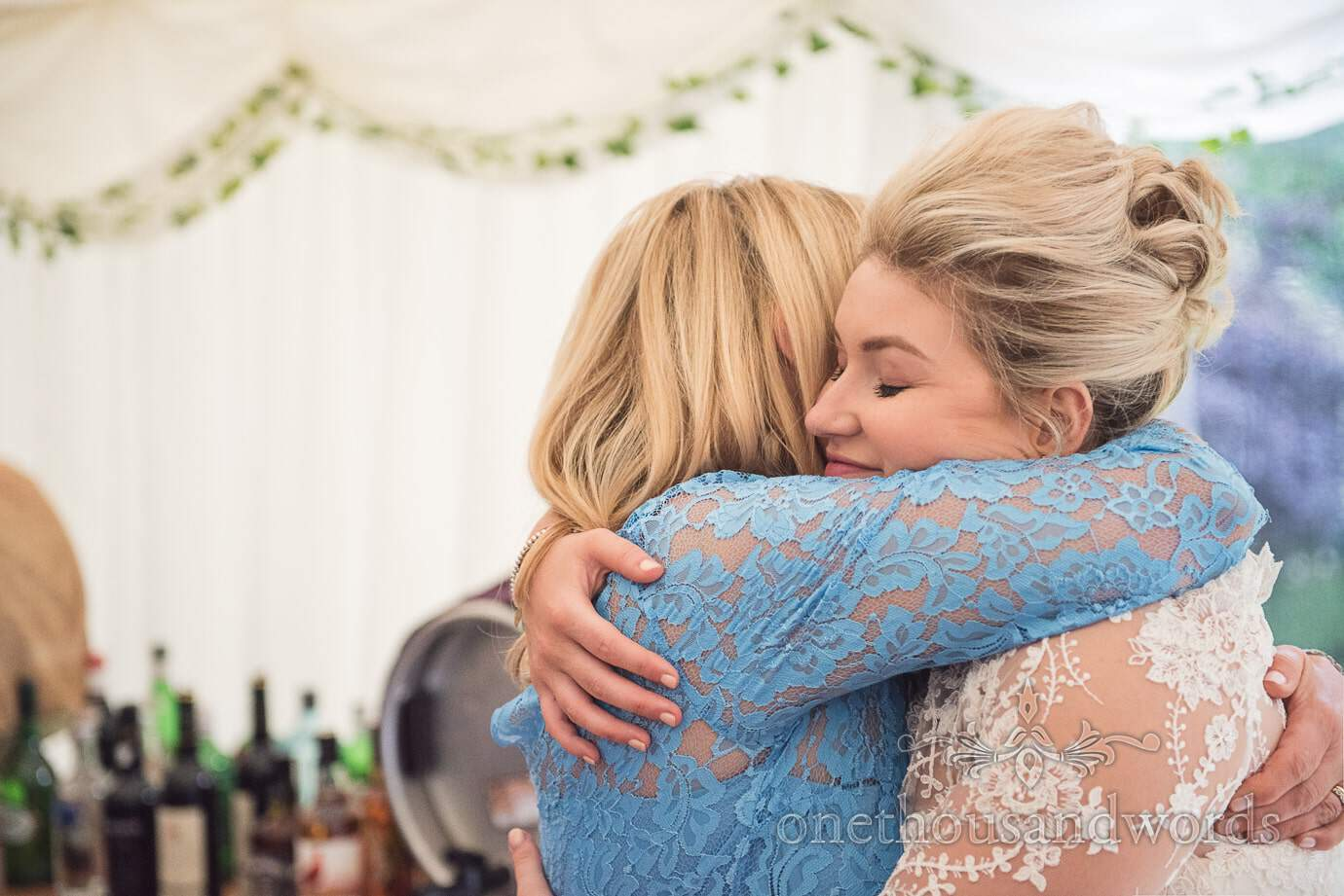 Bride hugs her mother in country wedding marquee in front of wedding bar