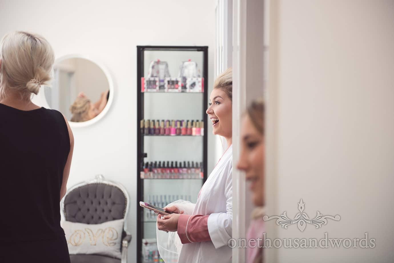 Bride in doorway at beauty salon laughs at wedding morning make-up preparations