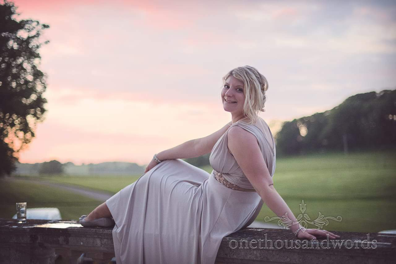 Bride in dusty silver dress enjoys the sunset at Lulworth Castle wedding