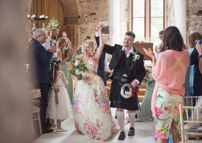 Bride in floral dress and groom in kilt walk down the aisle at Lulworth Castle wedding venue