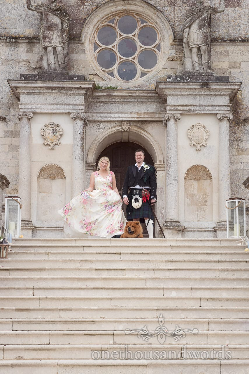Bride in floral dress, groom in kilt with chow chow dog on steps at Lulworth Castle wedding