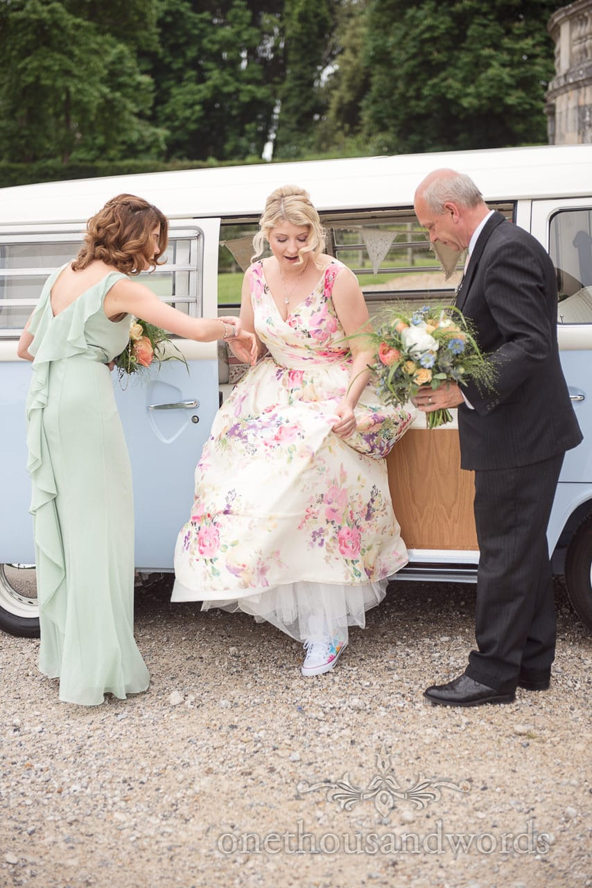 Bride in floral print wedding dress is helped out of van