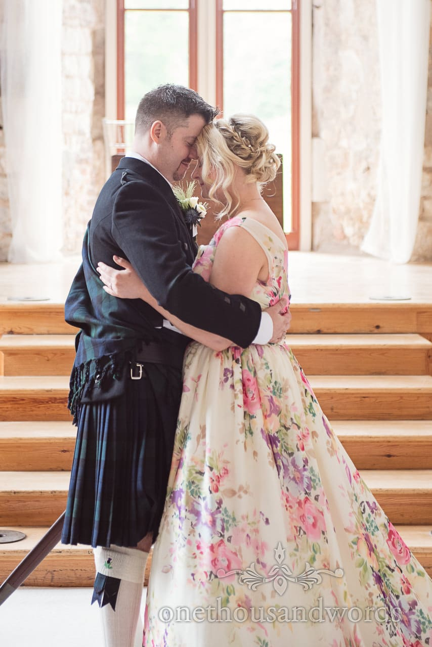 Bride in floral wedding dress and groom in kilt embrace at Lulworth Castle wedding ceremony