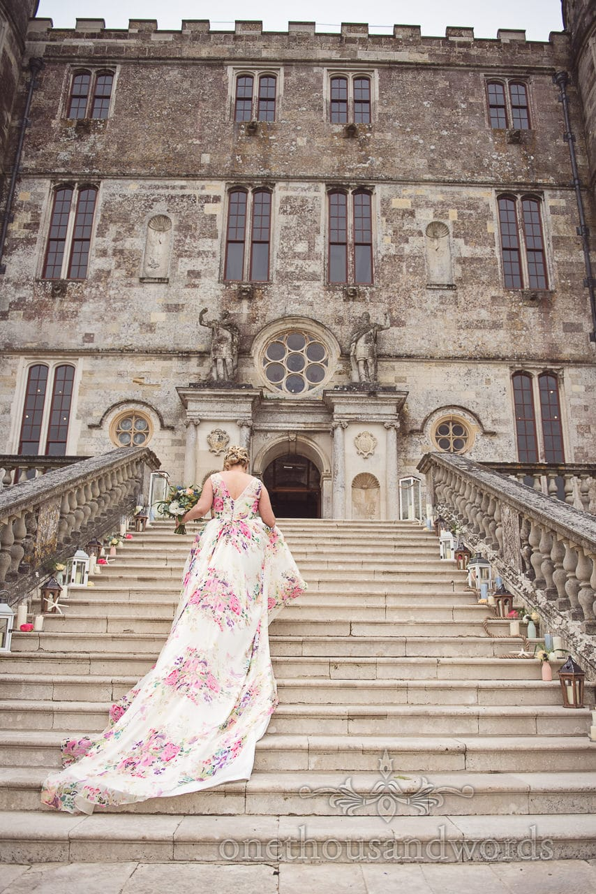 Bride in floral wedding dress climbs staircase at Lulworth castle wedding