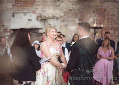 Bride in floral wedding dress smiles during civil wedding ceremony at Lulworth Castle