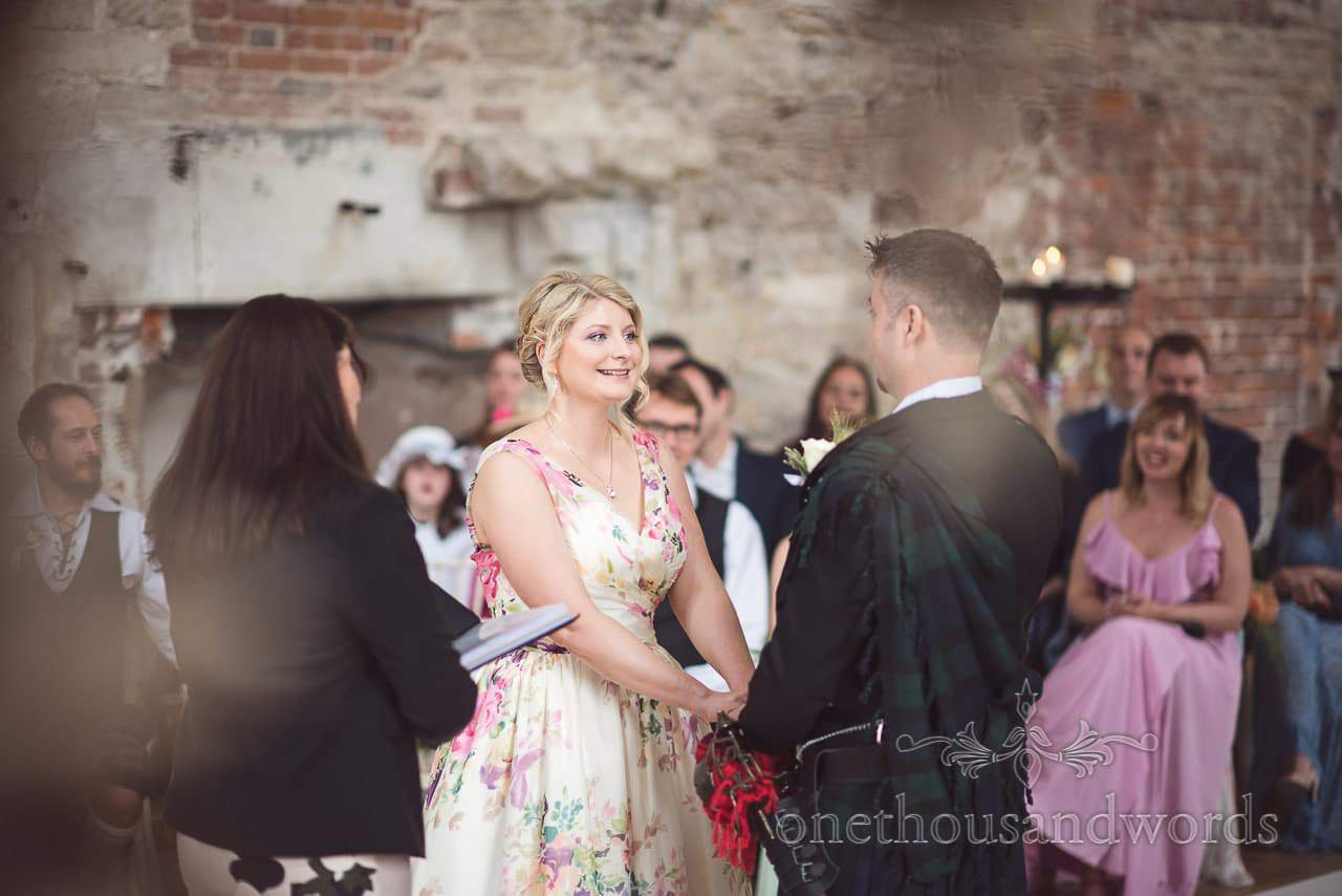 Bride in floral wedding dress smiles during civil wedding ceremony at Lulworth Castle