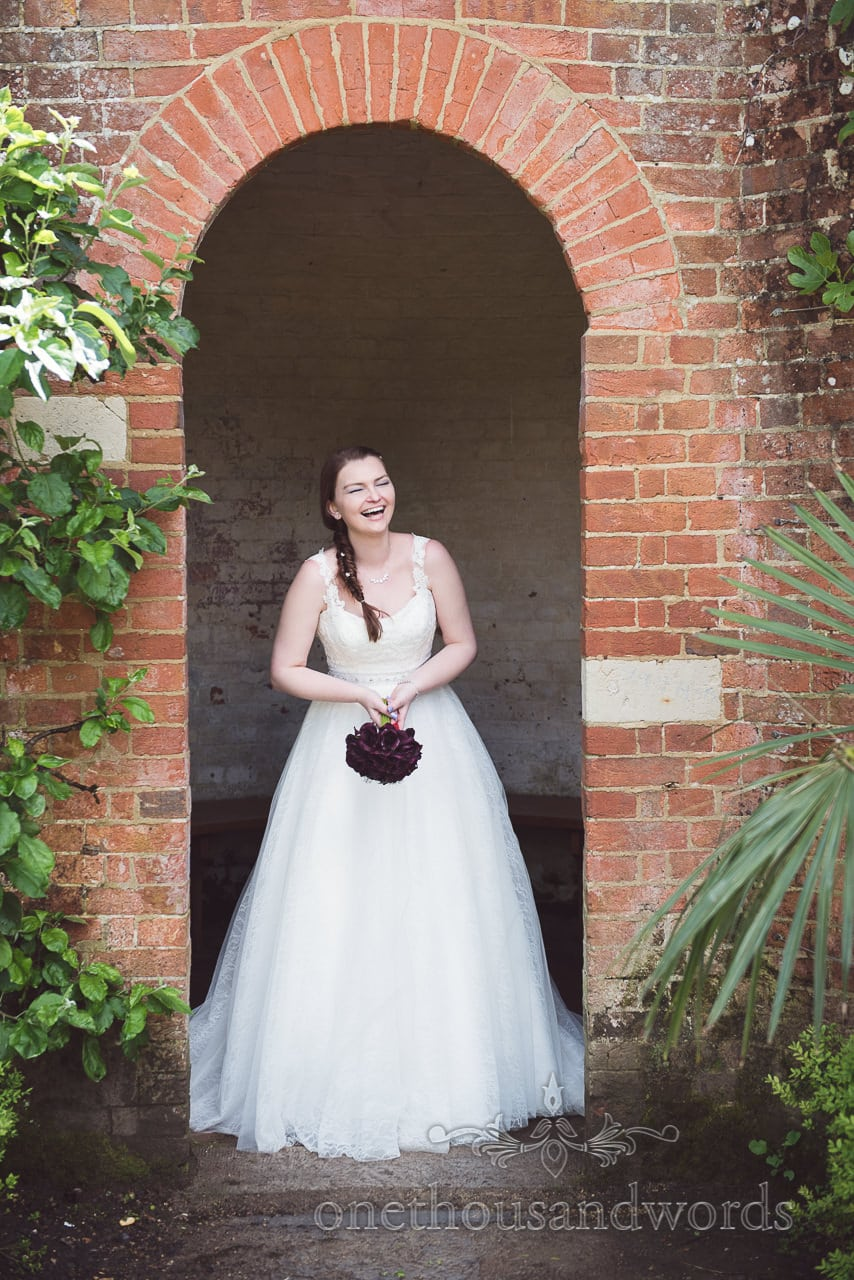 Bride in red brick archway at Upton House country park wedding in Dorset