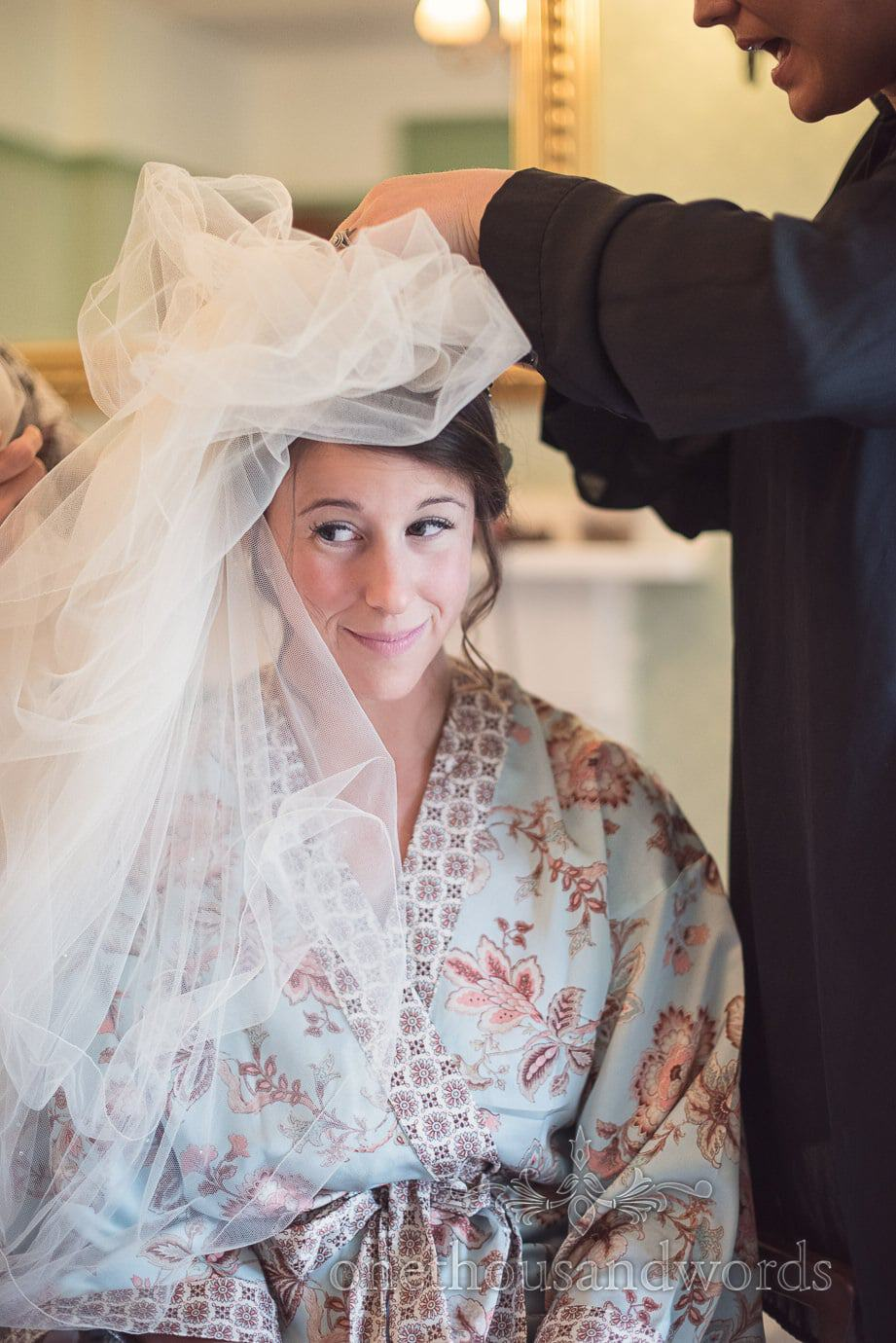 Bride in retro patterned sky blue dressing gown has veil attached to wedding hair