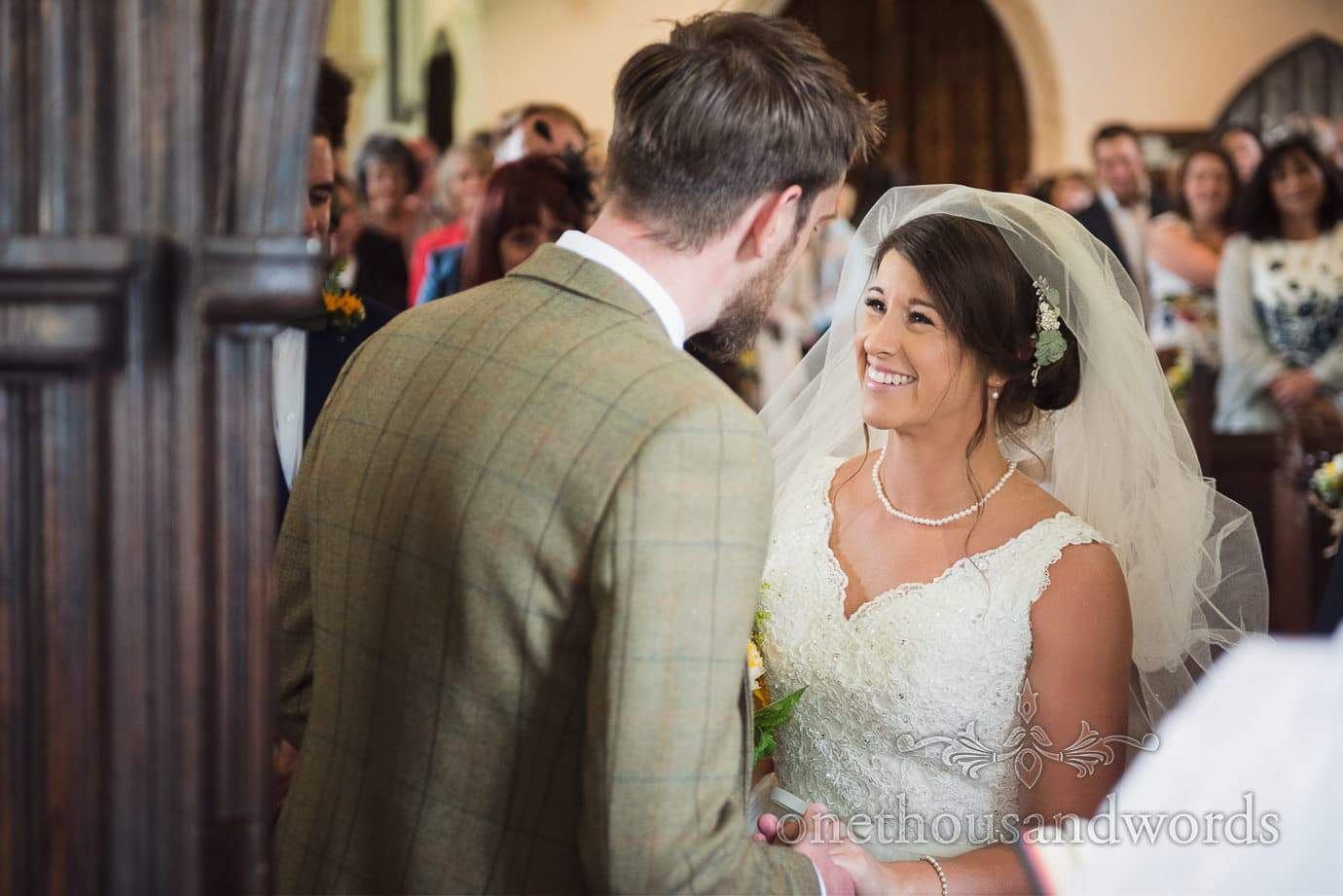 bride in veil and pearls smiles at groom during rustic English church wedding ceremony