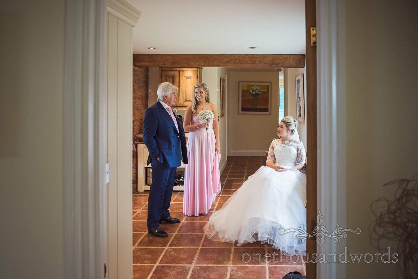 Bride in white dress waits with father and bridesmaid at home before church wedding