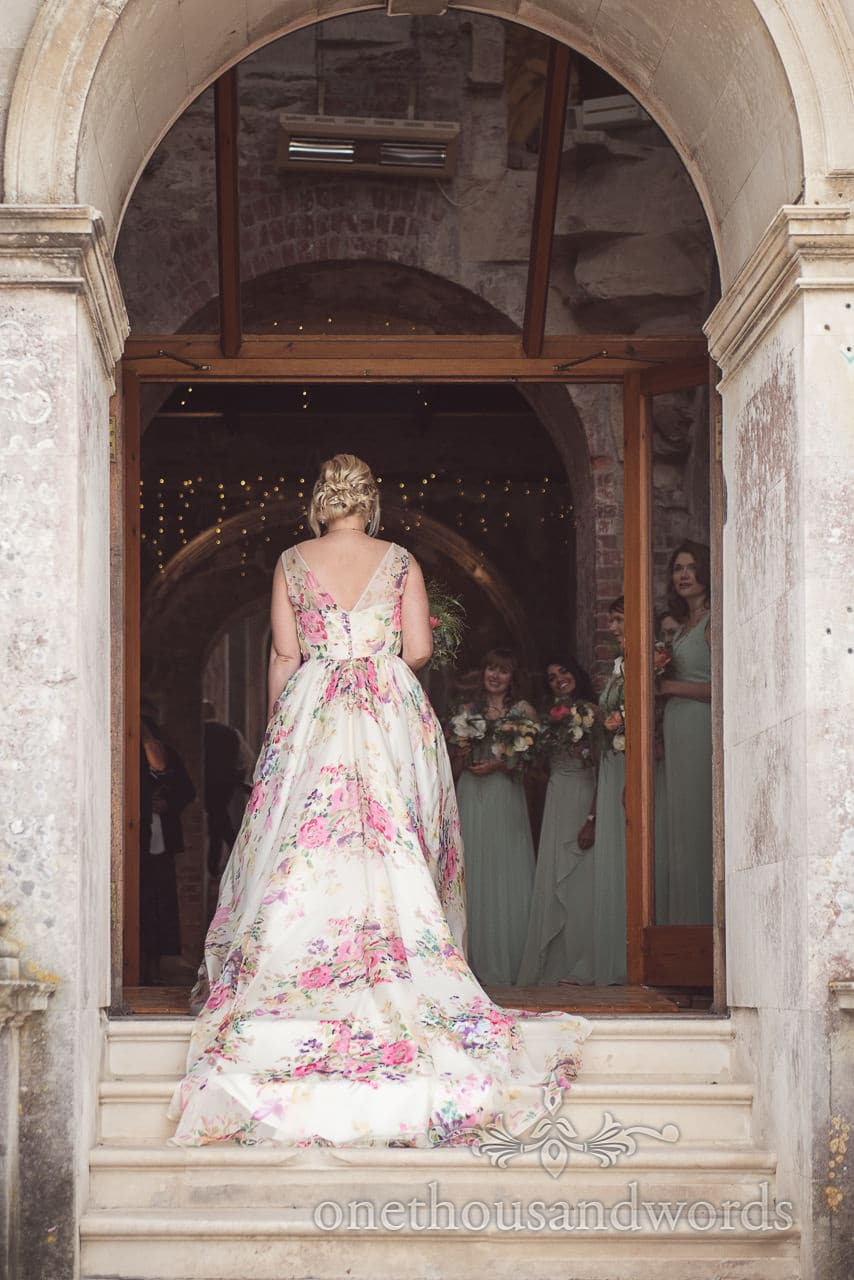 Bride is greeted by bridesmaid in hallway at Lulworth castle wedding