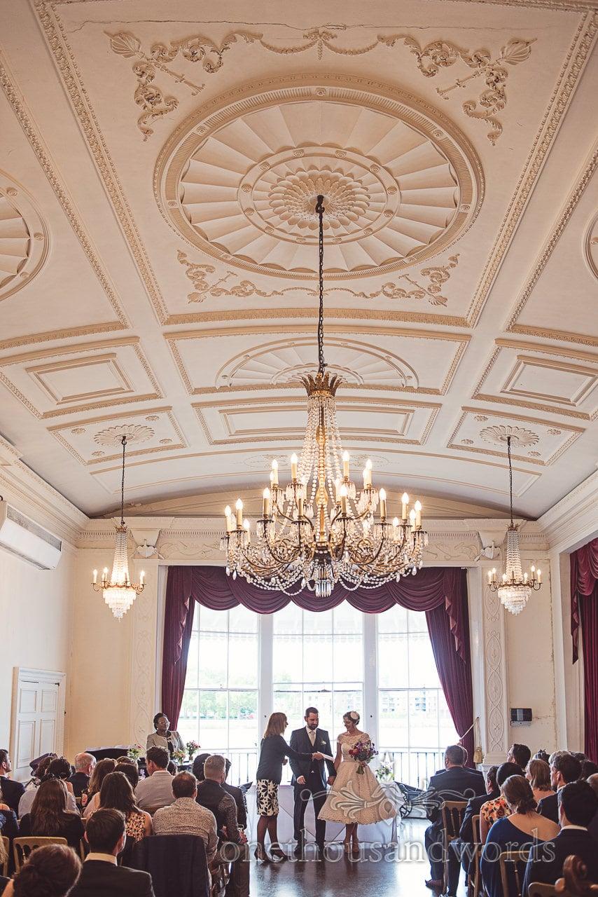 Bride is presented with marriage certificate in Nelson room at Trafalgar Tavern wedding under huge chandelier