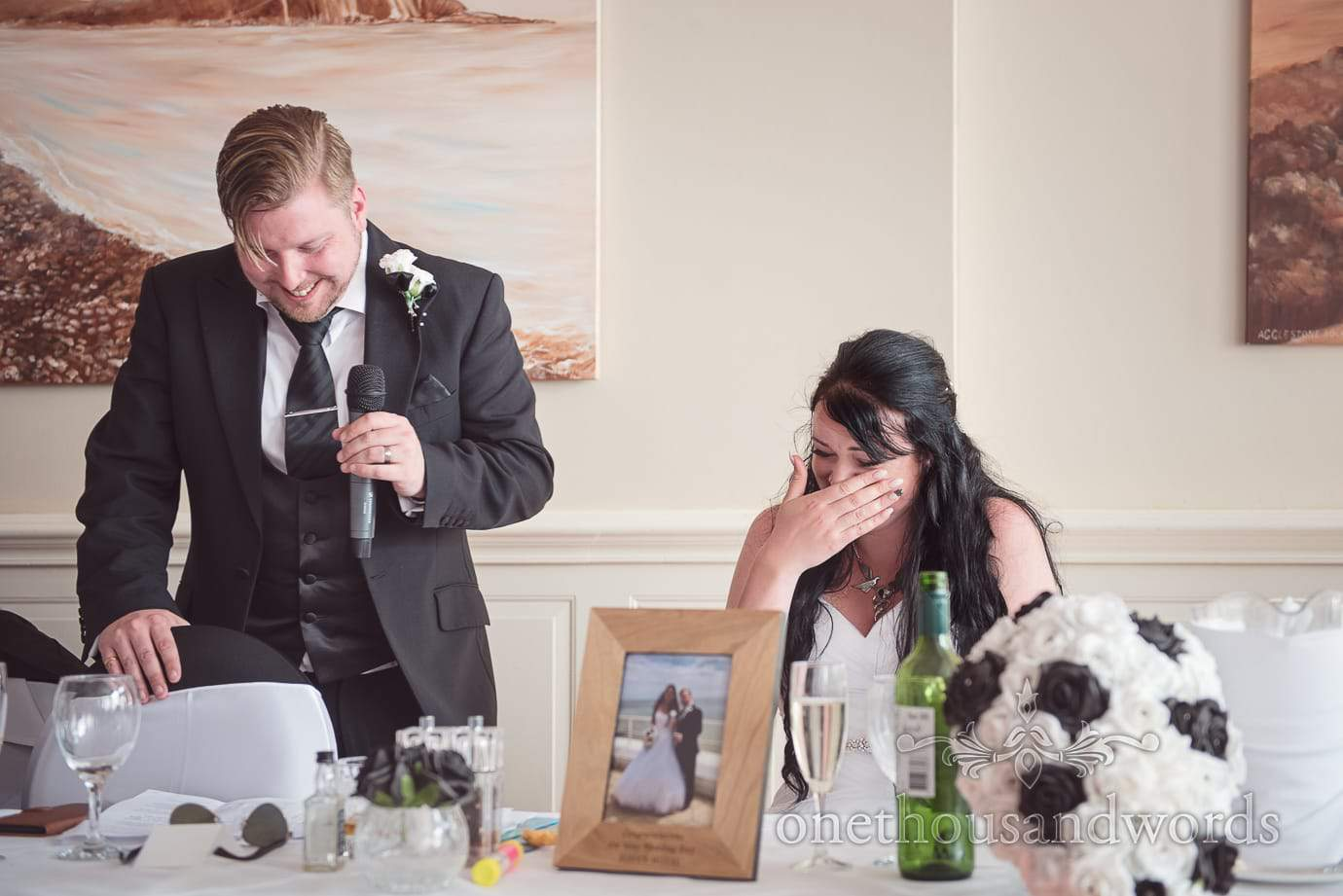 Bride laughs at grooms speech at black and white rock and roll themed wedding