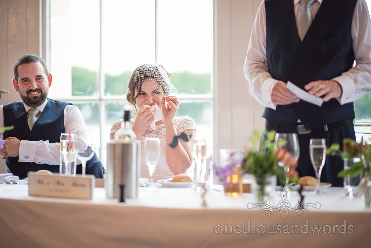 Bride laughs at wedding speeches at Greenwich wedding photographs