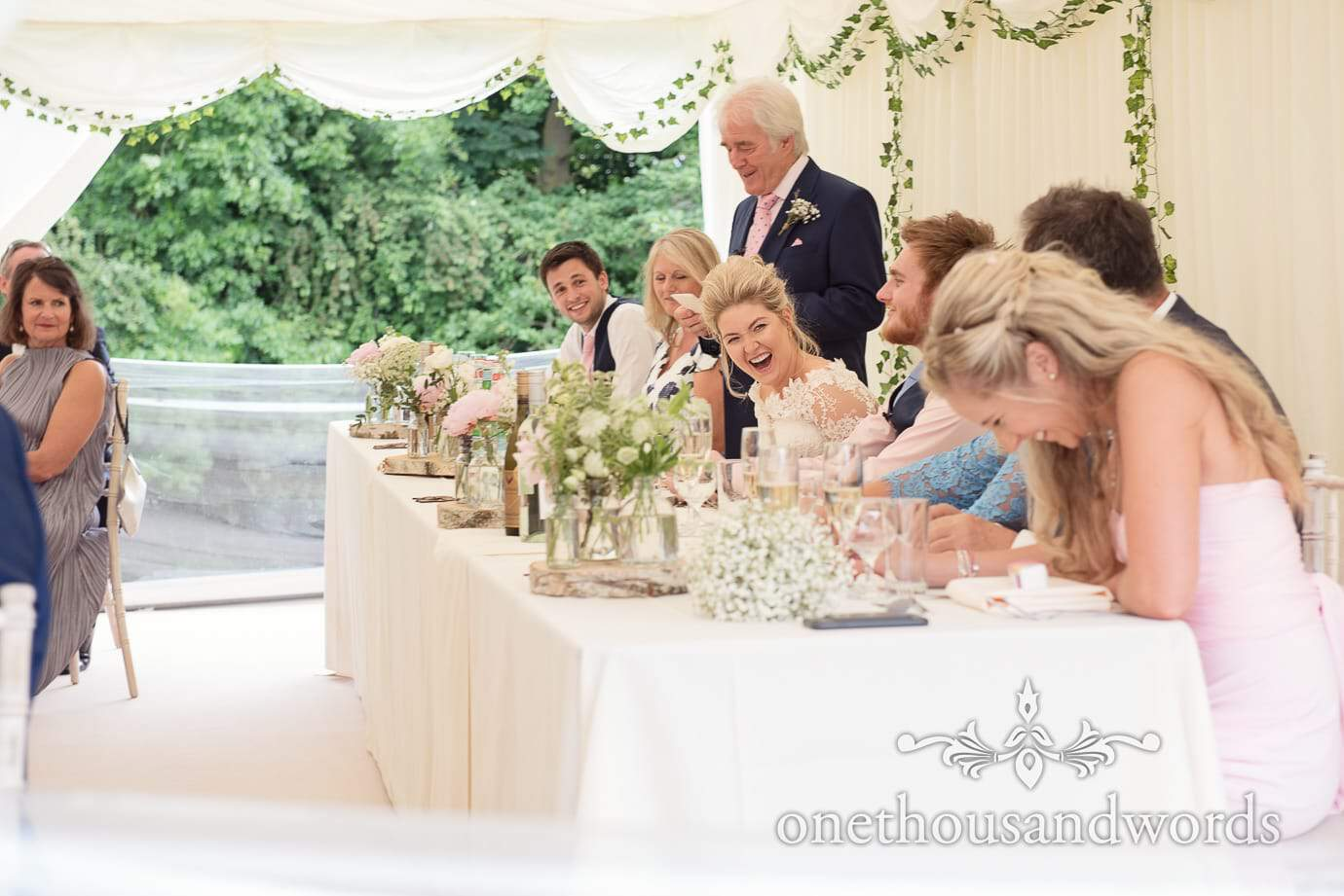 Bride laughs on country wedding marquee top table to fathers wedding speech