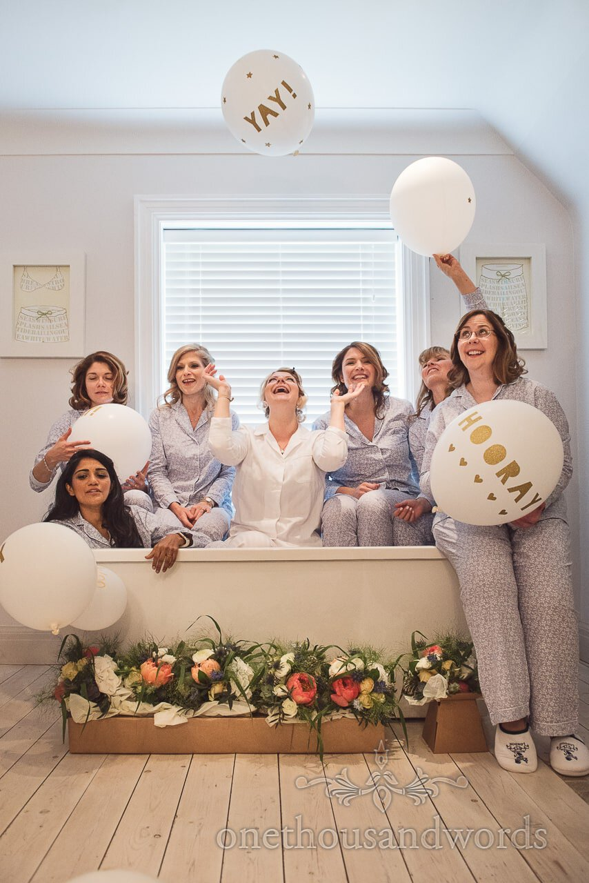 Bride poses with bridesmaids in bath with balloons and flowers