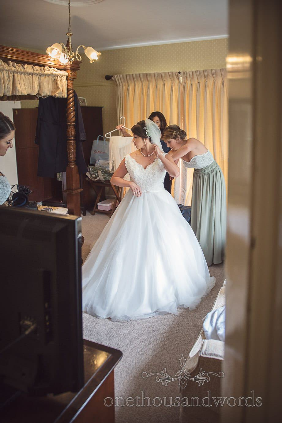 Bride puts on white wedding dress in hotel room with four poster wooden bed