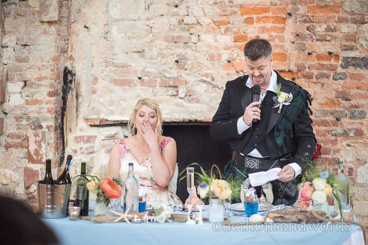 Bride reacts to groom's wedding speech in ruined castle wedding venue in Dorset