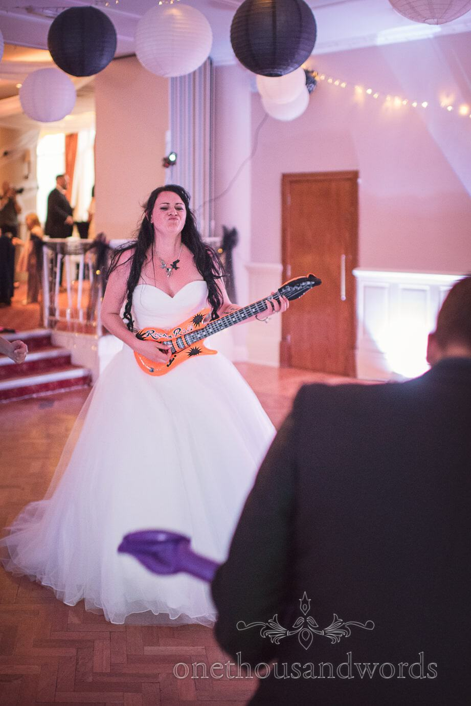 Bride rocks out playing inflatable guitar at Rock and Roll themed wedding photograph
