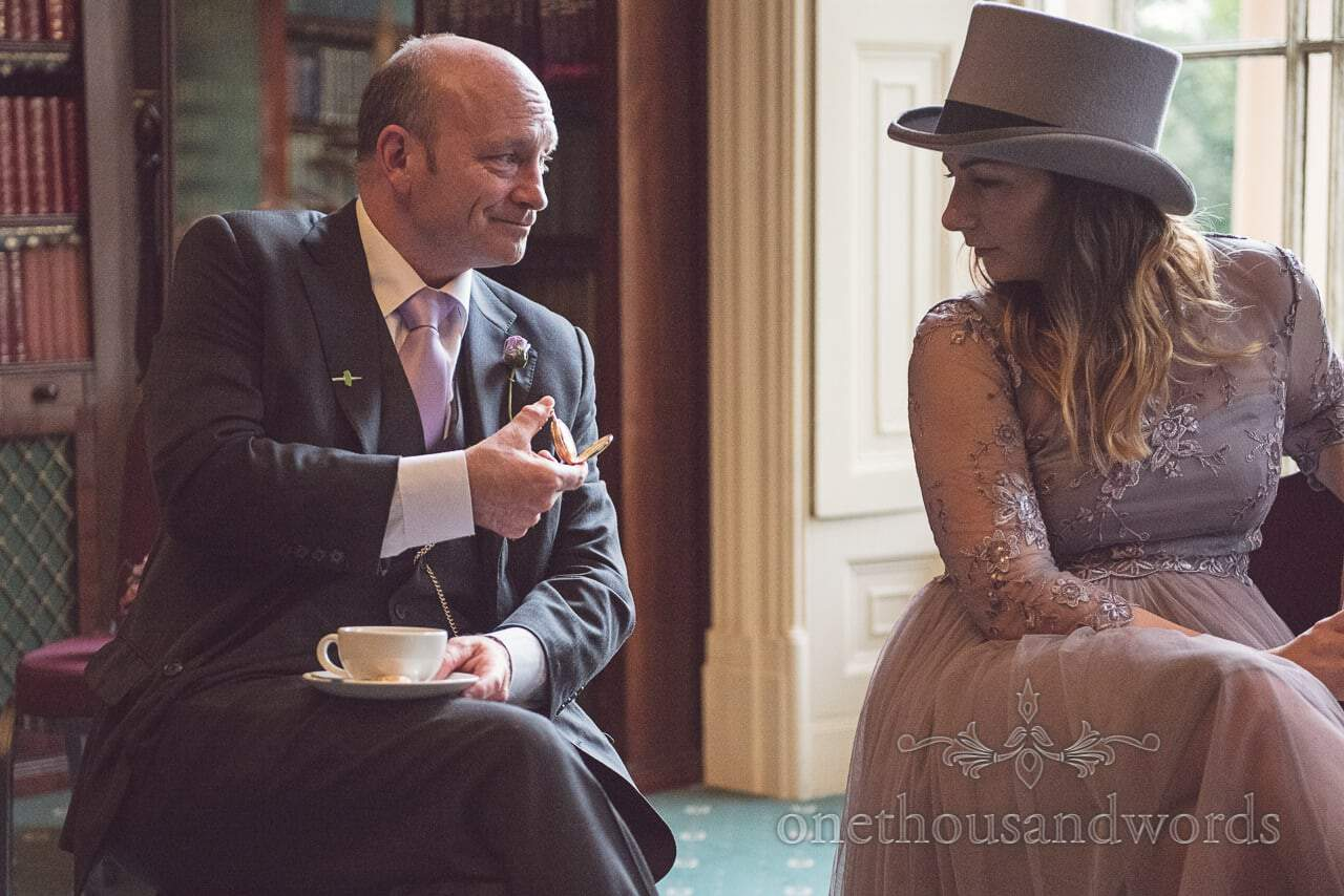 Bride's father shows off gold pocket watch to bridesmaid in top hat at Upton House wedding