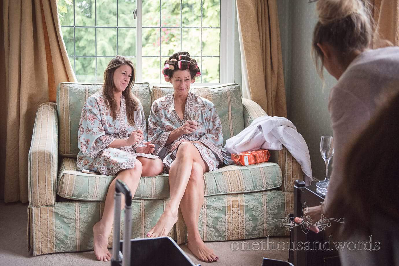 Bride's mother and sister in matching dressing gowns and hair curlers on wedding morning