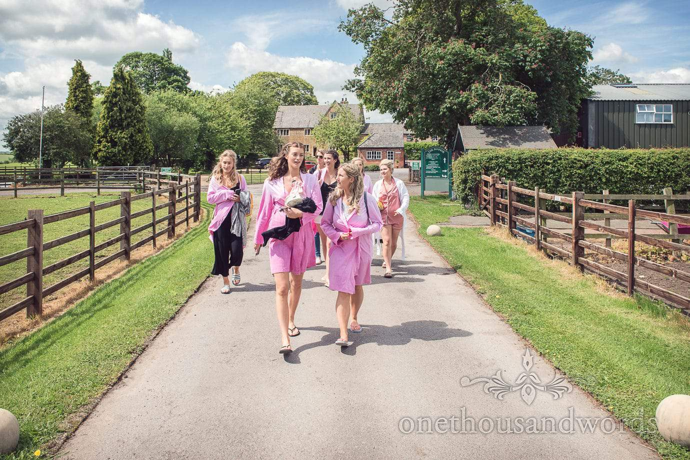 Bride's party in pink dressing gowns walk through country village on wedding morning in Leicestershire