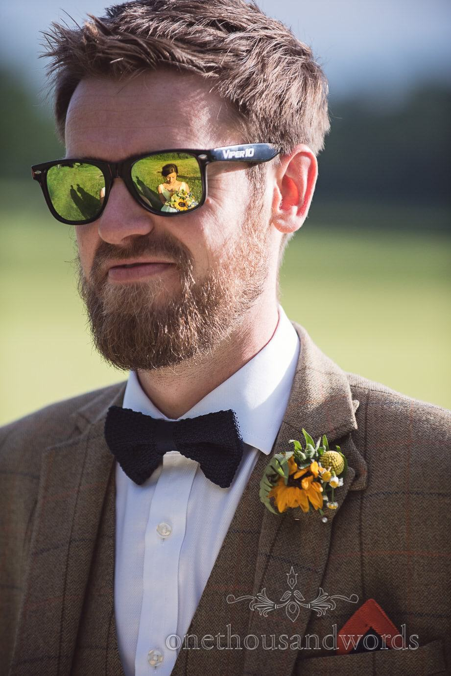 Bride's reflection in groom's yellow sunglasses at rustic wedding in the countryside