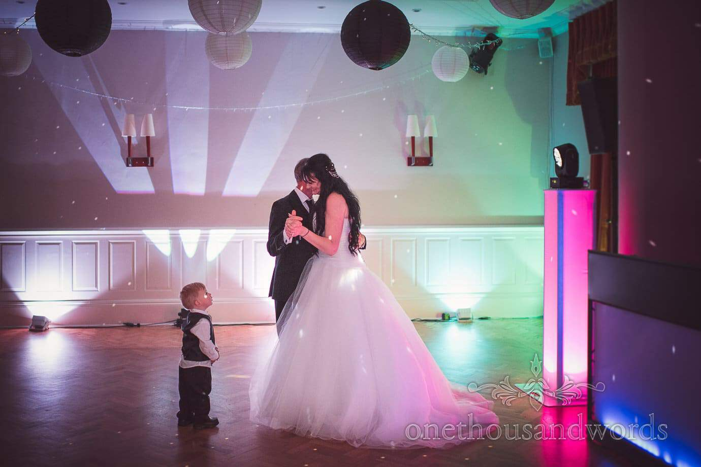 Bride's son curiously looks on during father daughter dance at black and white themed wedding
