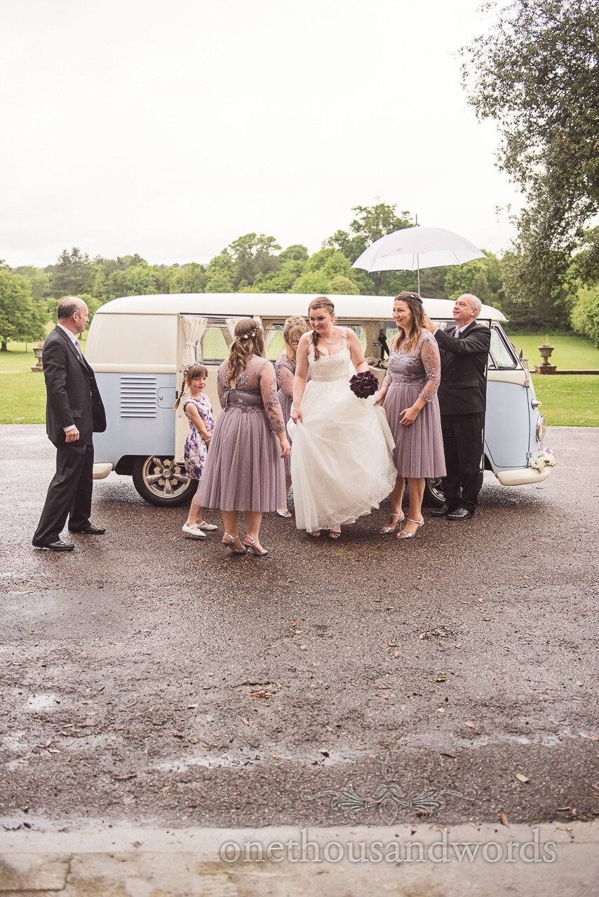 Bride steps out of classic VW wedding van in the rain at Upton House wedding