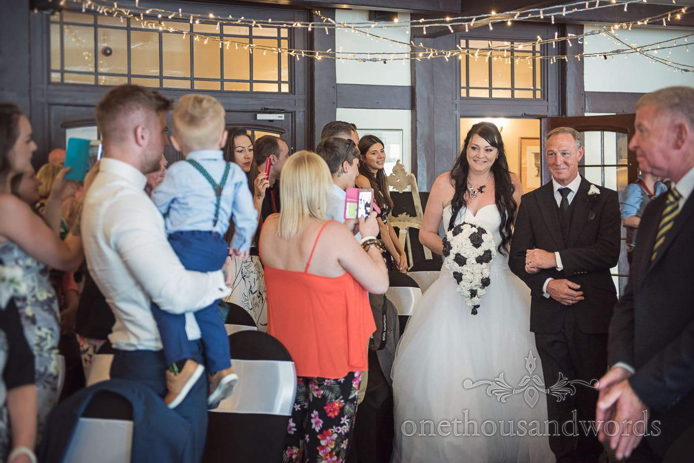 Bride with black and white wedding bouquet walks up the aisle at Haven Hotel wedding ceremony