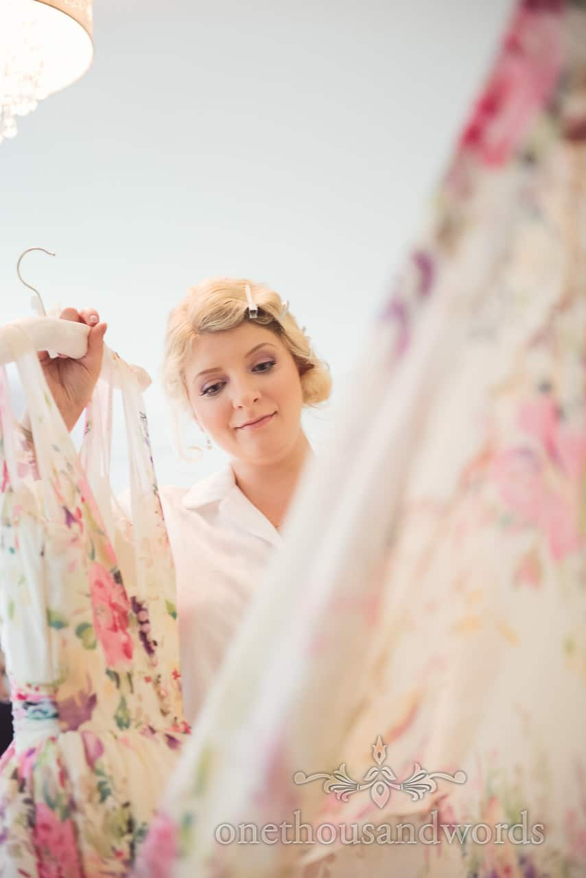 Bride with floral wedding dress on morning of Lulworth castle wedding
