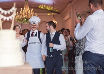 Brides brother in chef's hat and apron admiring home made wedding cake