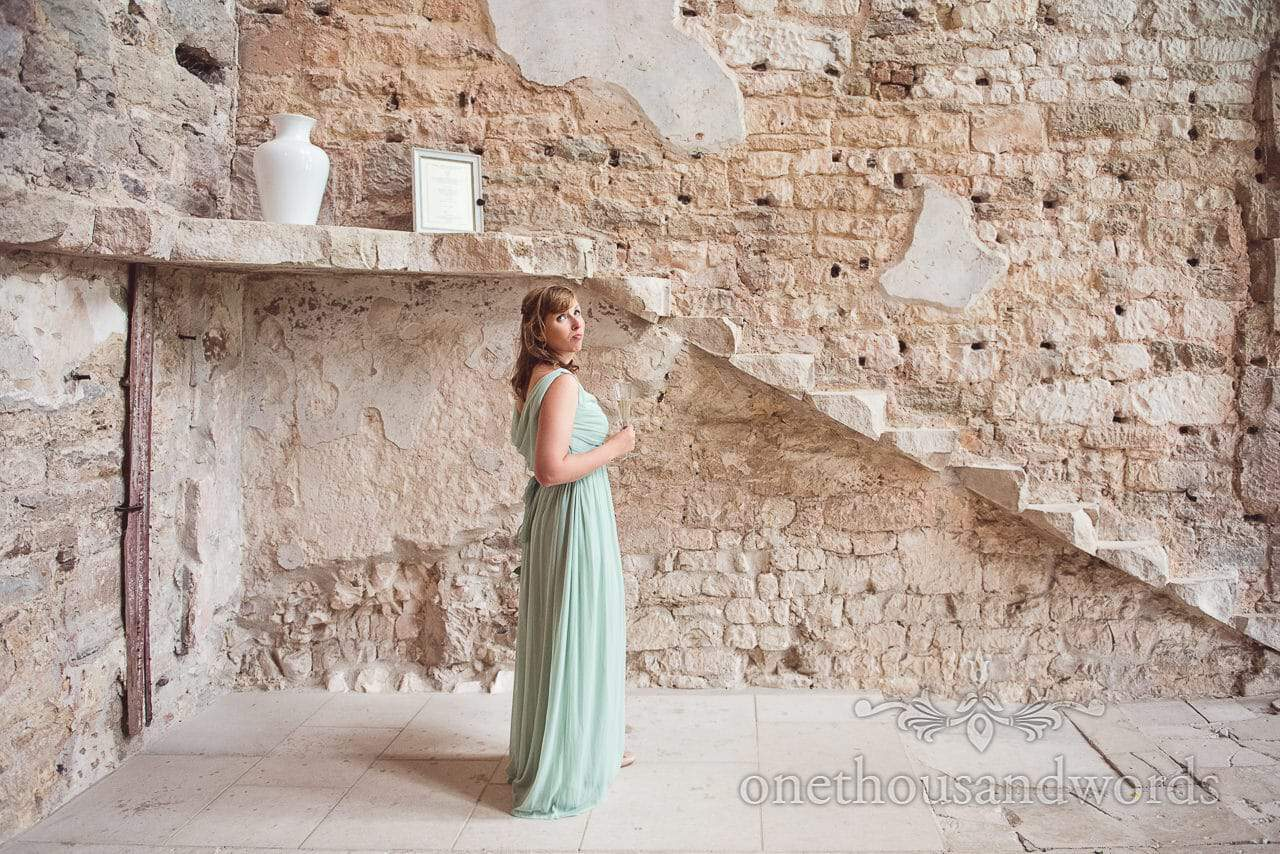 Bridesmaid against ruined castle walls and staircase at Lulworth Castle wedding venue