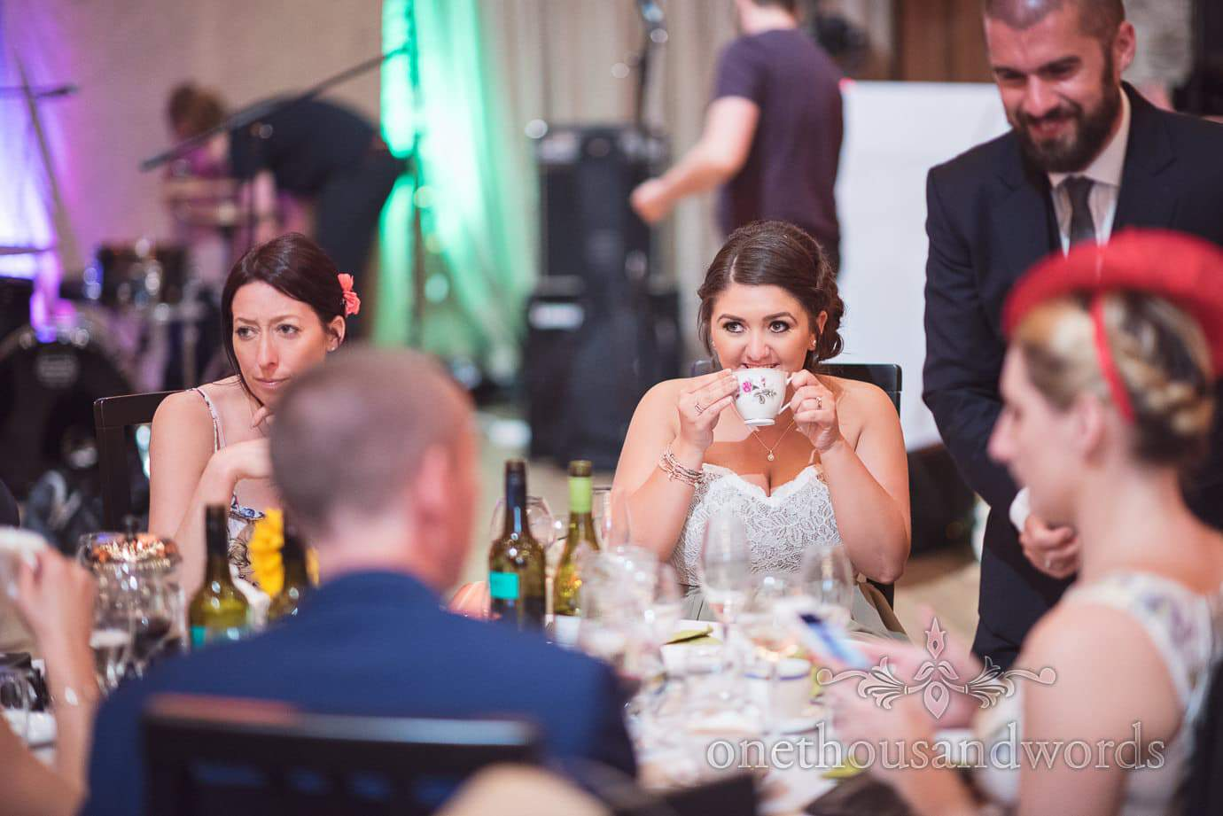 Bridesmaid drinks from a china tea cup at rustic barn wedding reception
