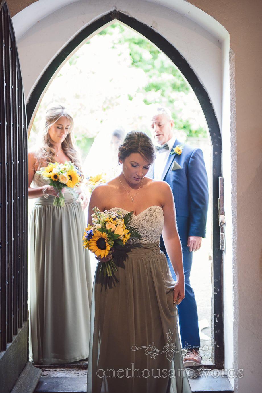 Bridesmaid in dusty green dress enters English church wedding in Dorset