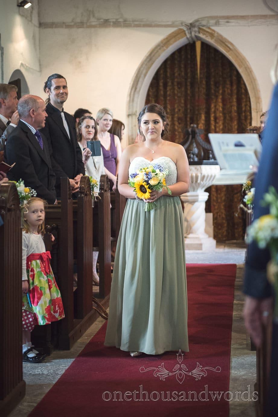 Bridesmaid in dusty green dress with sunflower bouquet walks down church aisle