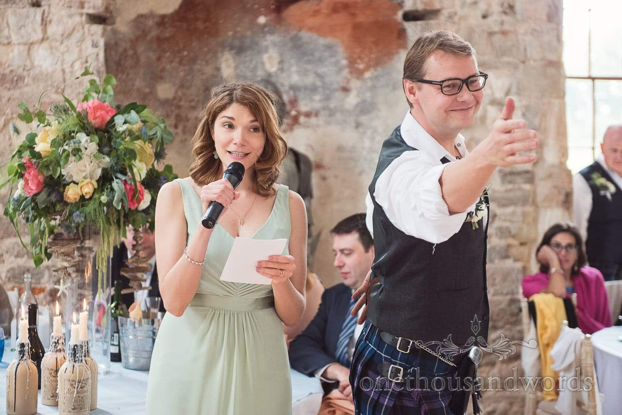 Bridesmaid in dusty pink bridesmaid dress makes speech at Lulworth Castle wedding photography