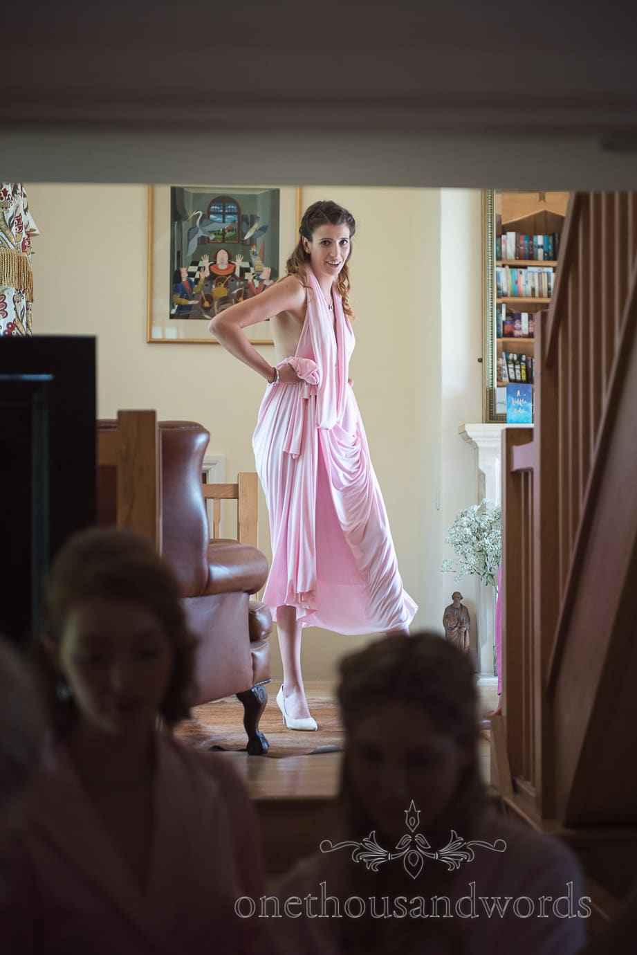 Bridesmaid in dusty pink Greco-Roman dress puts on white wedding shoes