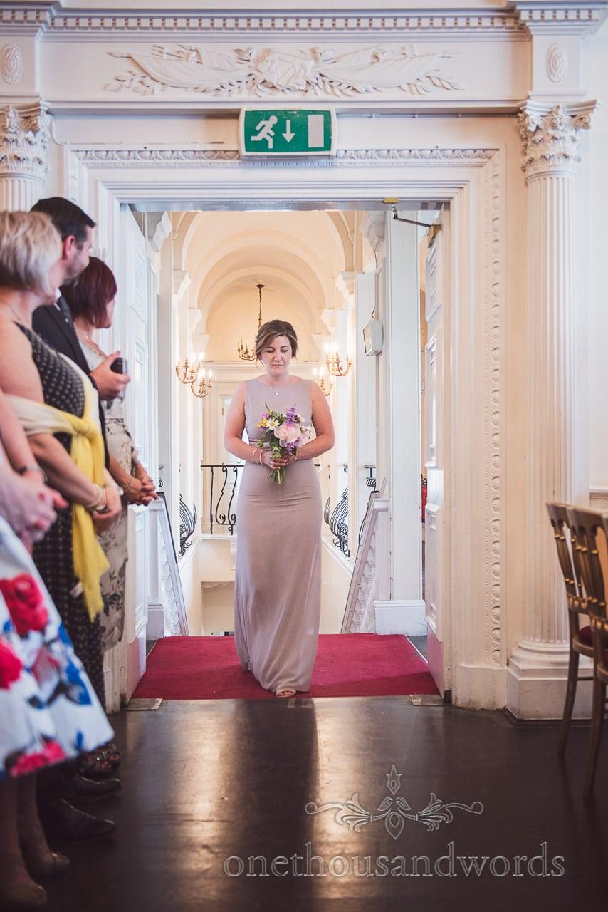 Bridesmaid in dusty violet bridesmaid dress enters wedding ceremony at Trafalgar Tavern