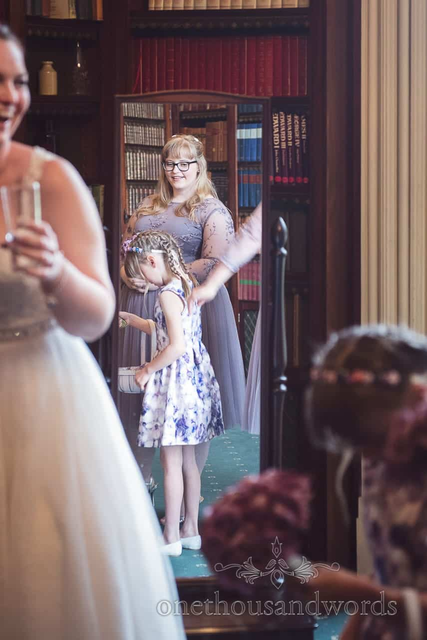 Bridesmaid in in dusty purple bridesmaid dress in library mirror at Upton House wedding