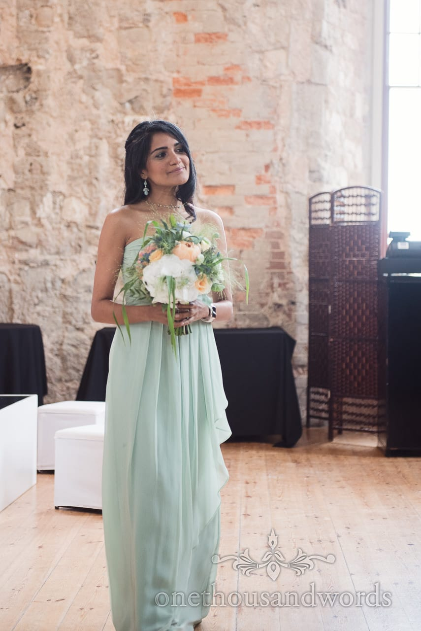 Bridesmaid in pale green dress enters the ceremony room at Lulworth castle wedding