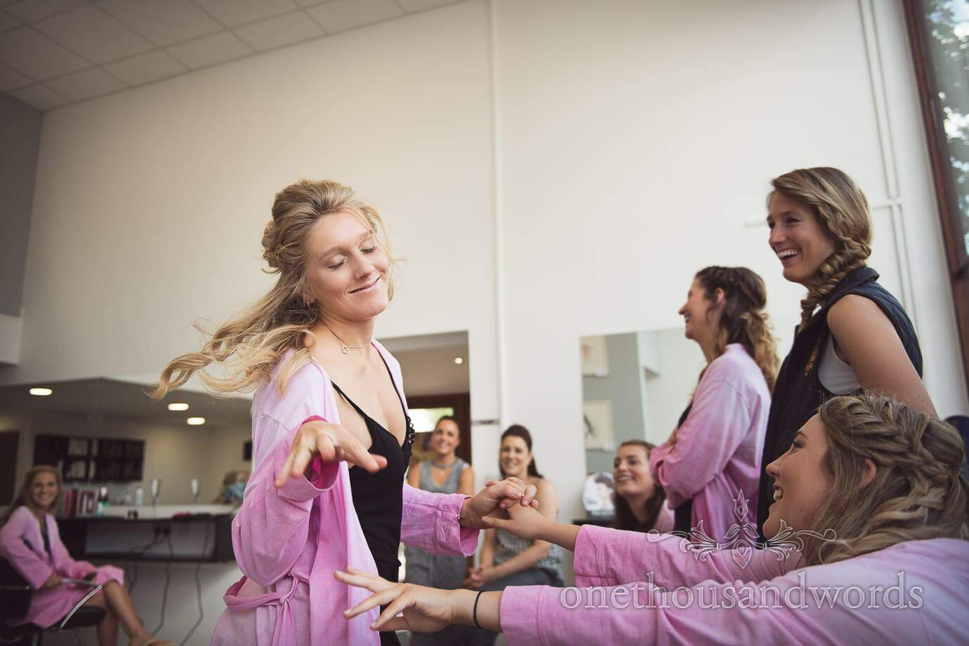 Bridesmaid in pink dressing gown shows of her wedding hair and make-up in beauty salon