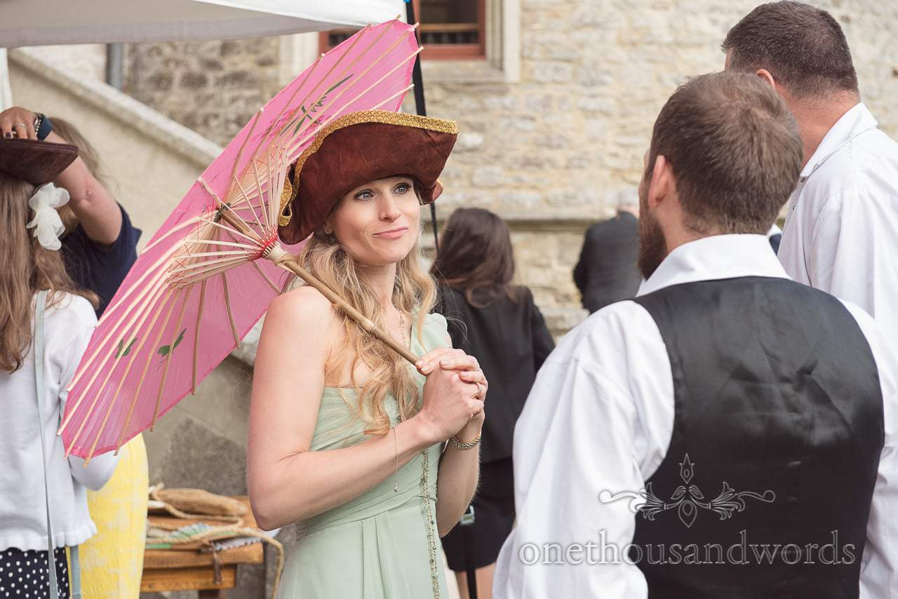 Bridesmaid in pirate hat and pink parasol at surprise pirate themed wedding