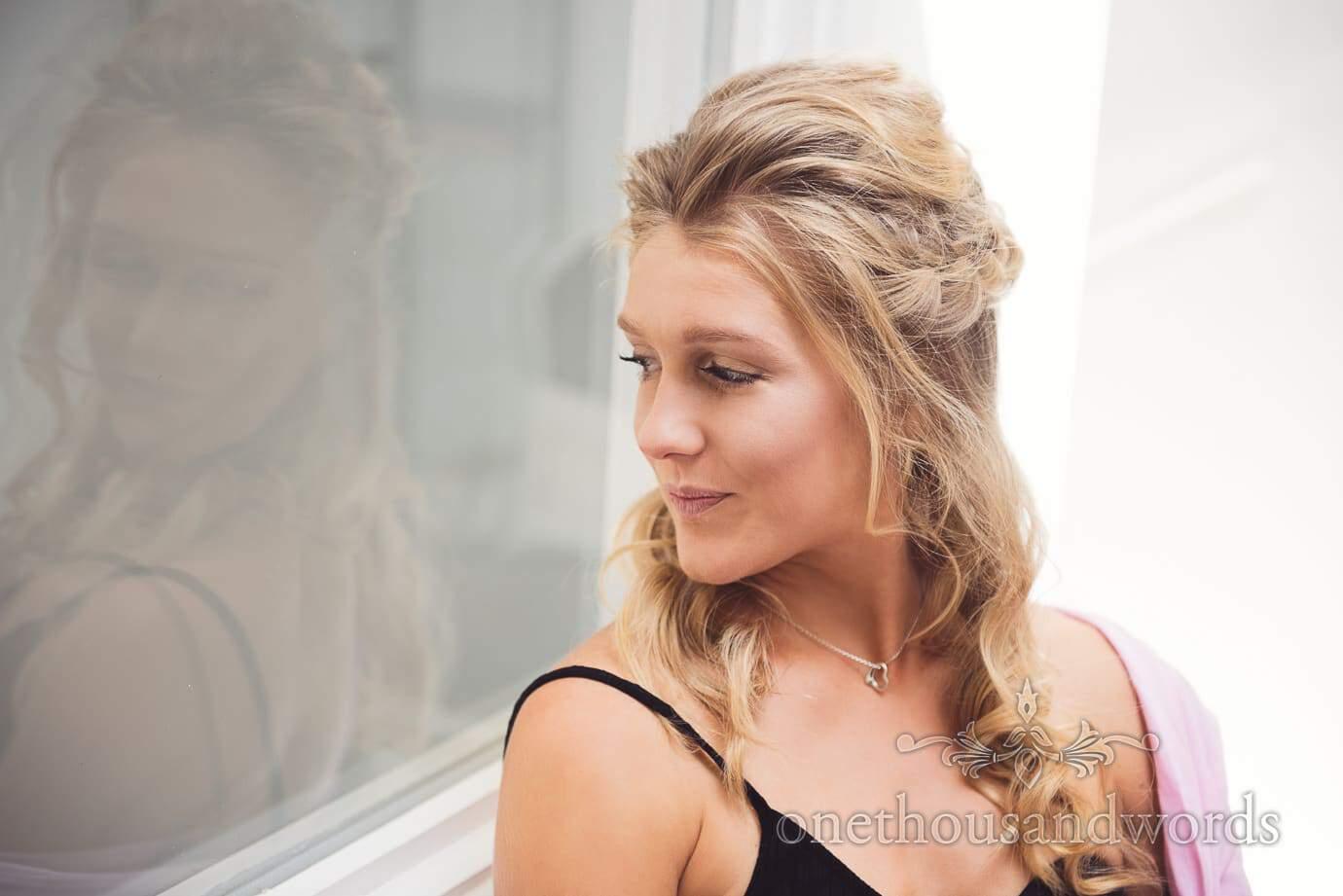 Bridesmaid in wedding make-up looks through beauty salon window on wedding morning