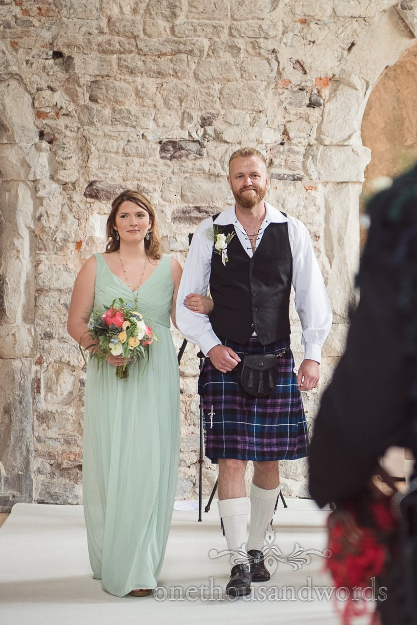 Bridesmaid is escorted down the aisle at Lulworth castle wedding