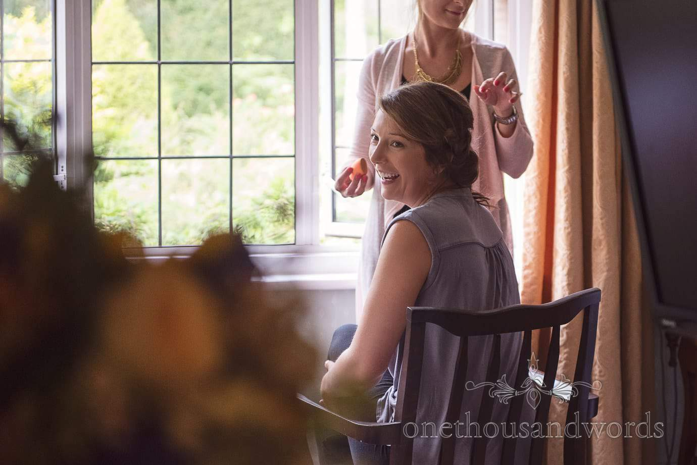 Bridesmaid laughing whilst having wedding make up styled in Hotel window