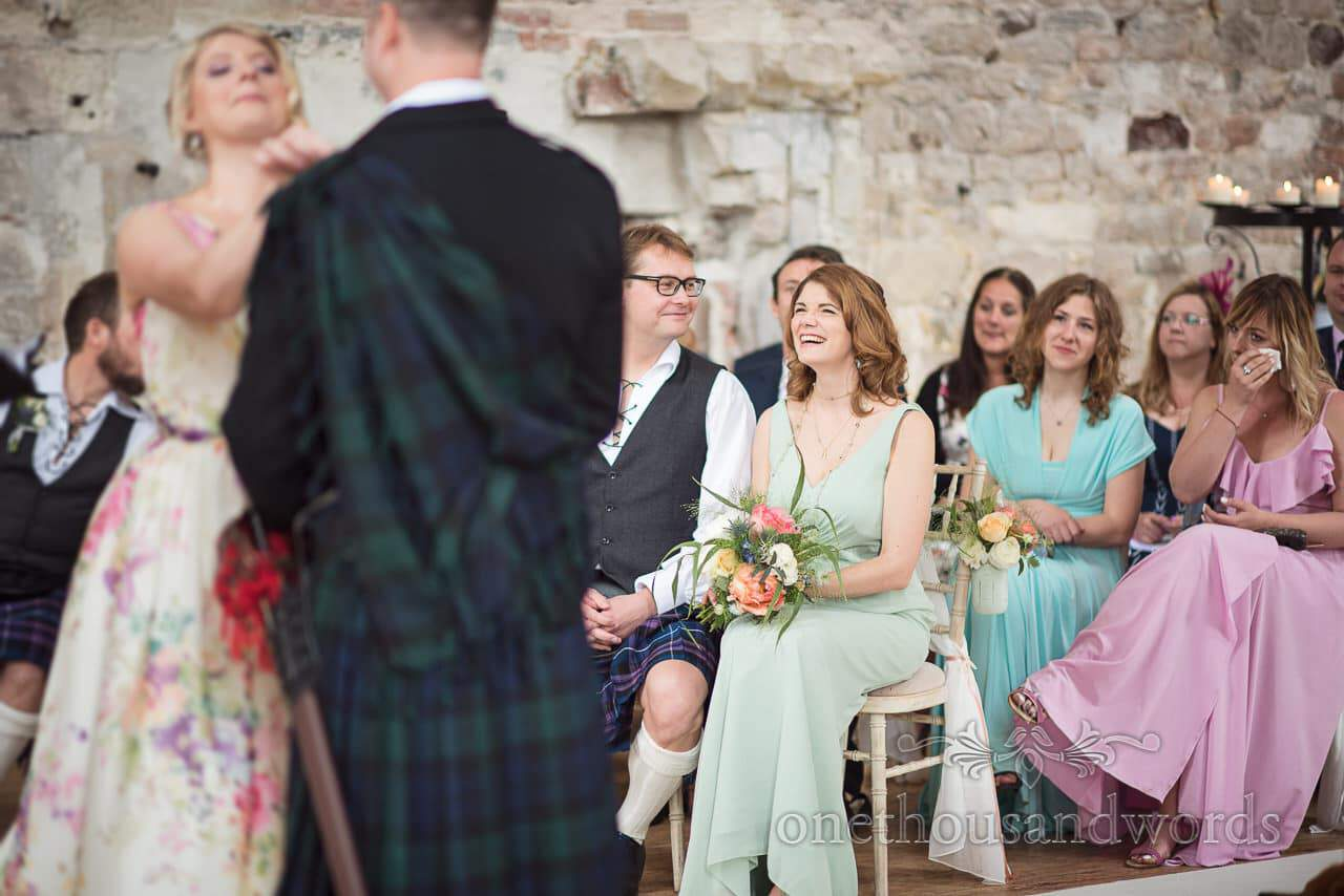 Bridesmaid laughs and wedding guests cry at civil wedding ceremony in ruined castle